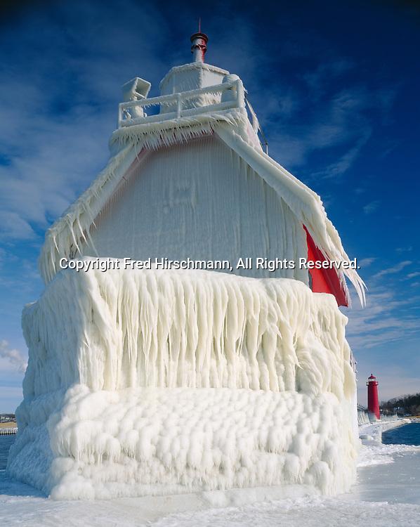 Ice-covered Grand Haven South Pierhead Lighthouse with Grand Haven Inner Lighthouse beyond, Grand River, Lake Michigan, Grand Haven State Park, Grand Haven, Michigan.
