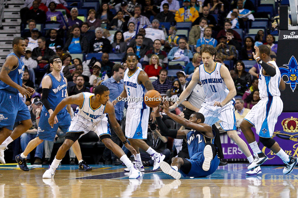 February 1, 2011; New Orleans, LA, USA; Washington Wizards point guard John Wall (2) passes from the floor as New Orleans Hornets small forward Trevor Ariza (1) and center David Andersen (11) defend during the second quarter at the New Orleans Arena.   Mandatory Credit: Derick E. Hingle
