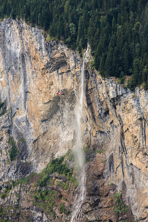 Swiss flag hanging from cliffs by waterfall, Switzerland