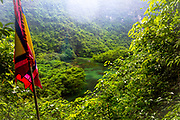 Red flag in the foreground of a high scenic look out point over the lake and other mountains in the back with mist, rain, fog. This is the view from the front of the Pagoda at Trang An. In the water is a small boat. RAW to Jpg