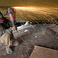 Workers in a boatyard on the Buriganga river in Dhaka, Bangladesh, welding and grinding the hull of a boat
