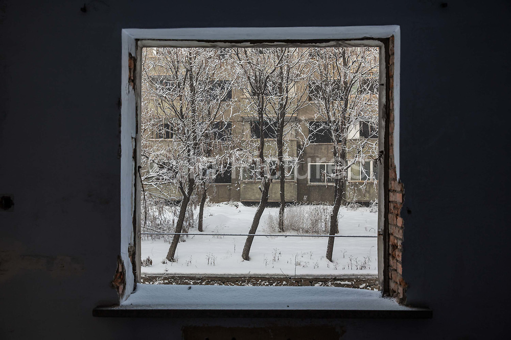 A view out the window of an abandoned workers housing complex near a Tonghua Iron & Steel Group Co. plant in the distance in the Erdaojiang district in Tonghua, Jilin province, China, on Wednesday, Jan. 6, 2016. The citys once-vaunted state-run steel mills have slipped inexorably into decline, weighed down by slumping global markets, a changing economy, and the burden of costs and responsibilities to the people of the town they fostered. Previous attempts to privatise the enterprise have met with stiff resistance, one such attempt resulted the mob lynching and death of a private businessman who wanted to invest and streamline the operation.