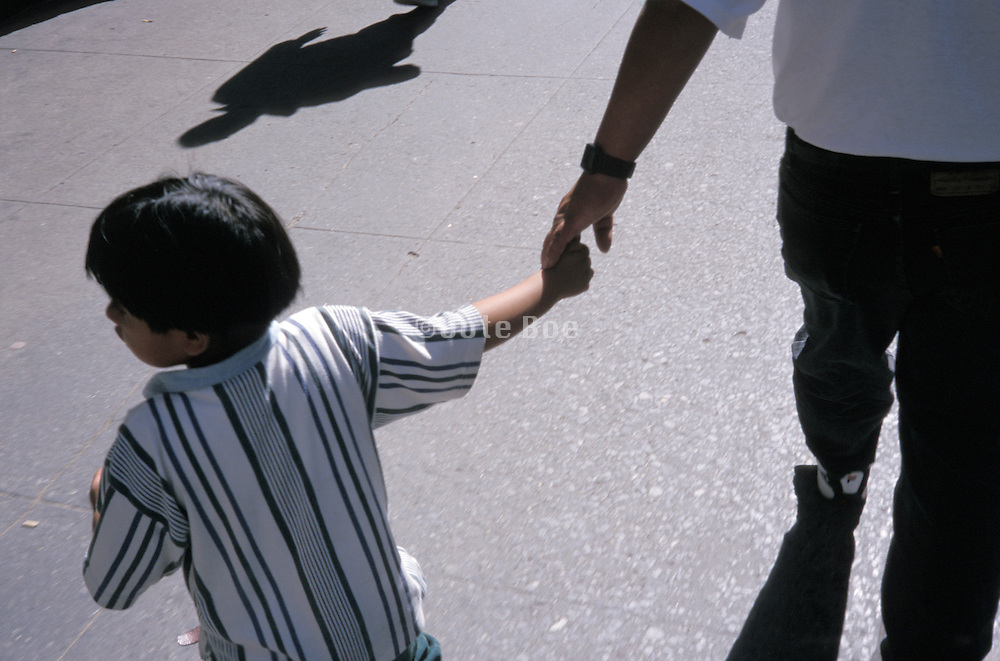 A young boy pulling his father back