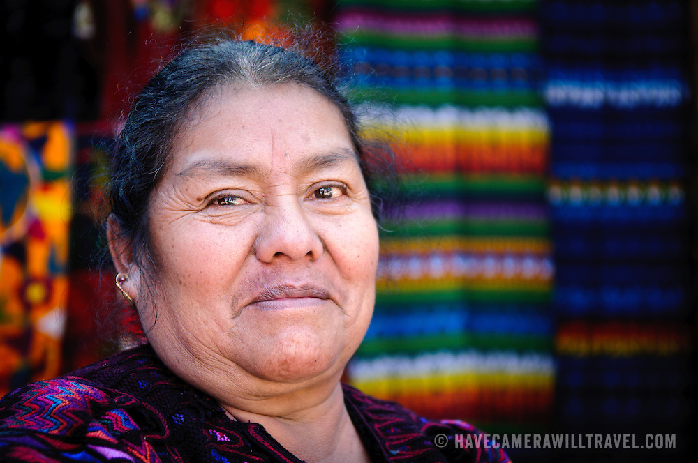 A local weaver poses for a photo in front of her market stall. Chichicastenango is an indigenous Maya town in the Guatemalan highlands about 90 miles northwest of Guatemala City and at an elevation of nearly 6,500 feet. It is most famous for its markets on Sundays and Thursdays.