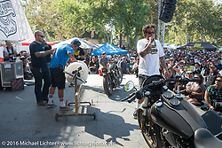 Mike Davis spins the drum for the Give-Away raffle ticket as Grant Peterson MC's at the Born Free 8 Motorcycle Show. Silverado, CA, USA. June 26, 2016.  Photography ©2016 Michael Lichter.