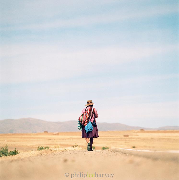 Woman walking through the Pampa de Siloli, Bolivia