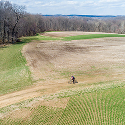 A man rides his mountain bike through a hay field in early spring in Elk Township, Pennsylvania.
