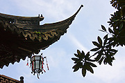 Chinese lantern hanging from traditional style roof, in the Yu Gardens, Shanghai, China