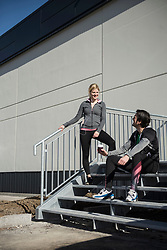 Man and woman in sportswear relaxing on steps after workout