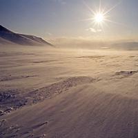 Spitsbergen Island, Svalbard, Norway. Spindrift snow blows over a polar glacier under the midnight sun.