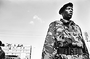 NAIROBI, KENYA - DECEMBER 31, 2007: A General Service Unit Soldier looks on as his brigade violently disperses a crowd of Orange Democratic Movement supporters. A surge in violence left scores of people dead in Nairobi as defeated presidential candidate Raila Odinga prepared to declare himself head of state, after rejecting the victory of incumbent president Mwai Kibaki. Despite news briefings for non-aggressive police action, a rising death toll reflected questionable methods from the General Service Unit, the paramilitary wing of Kenya's police charged with establishing order.