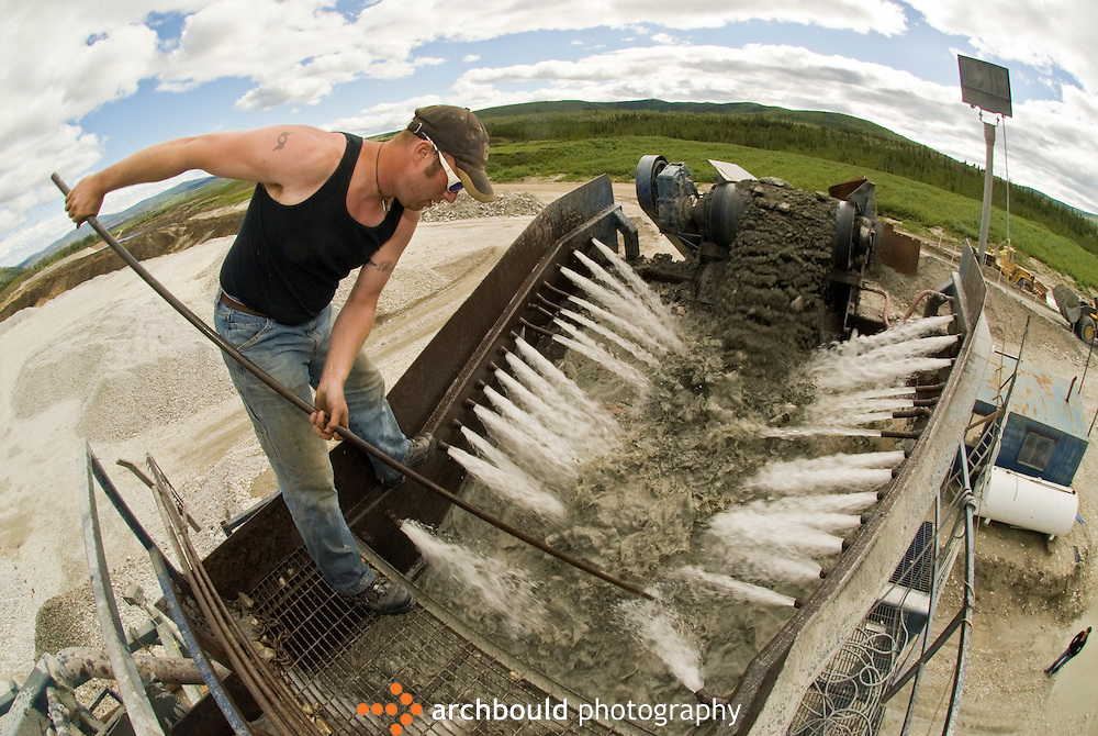 A gold mine worker feeds the gravel through the sluice in the Dawson gold fields.<br /> <br /> NOT IN YOUR BUDGET? Contact Cathie for a price specific to your project.