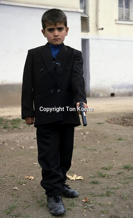 kid plays with a gun in tajikistan