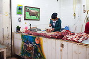 Young man cutting meat beef in a butchers stand, food market and traders selling their wares and goods on display, street scene, San Cristobal de las Casas, Chiapas, Mexico.