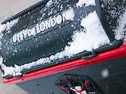 A City of London bin layered in snow, London, UK