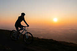 © Licensed to London News Pictures. 21/04/2019. Worcester, UK. A woman cycles after a religious service at sunrise on Easter Sunday, at the Worcestershire Beacon. The Beacon is the highest point in the Malvern Hills at 425m. Easter Sunday is a key date in the Christian calendar. Photo credit : Tom Nicholson/LNP