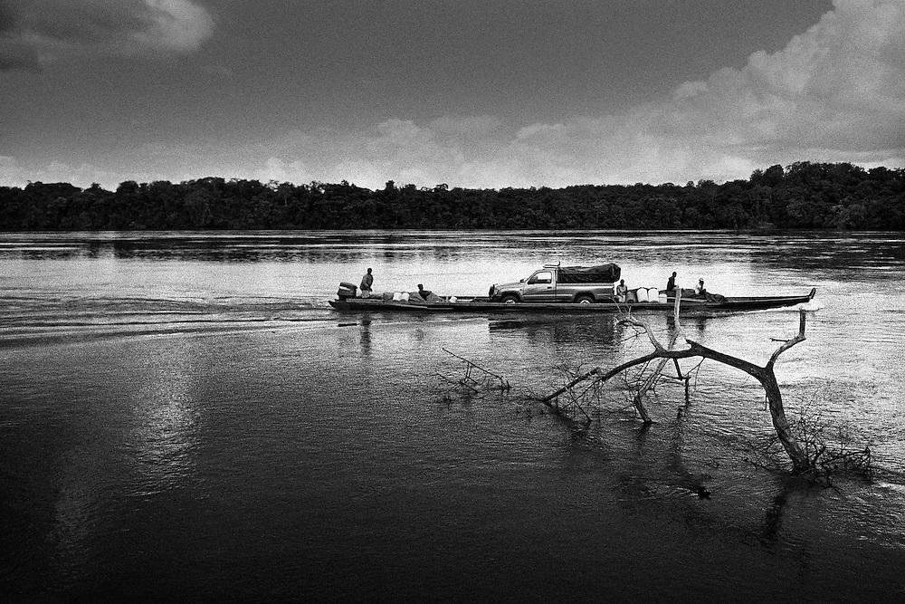 """Suriname, Camp Metal, maroni.<br /> <br /> Piroguiers bonis (noir marron) sur le Maroni, fleuve frontiere entre le surinam et la guyane francaise sur la totalite de son cours.<br /> <br /> Le Maroni nait dans la region des Tumuc-Humac et des massifs du Mitaraka, a la frontiere bresilienne, de la rencontre de 2 rivieres le Litany et le Marouini qui forment le Lawa au niveau du village d'Antecumpata. <br /> Le Lawa rencontre la Tapanahony a saut Poligoudi a 200 Km de l'estuaire. Ce n'est qu'a cet endroit que le fleuve se nomme veritablement Maroni jusqu'a l'ocean.<br /> Reconnu pour sa navigation difficile, le fleuve est jalonne de sauts aux noms evocateurs """" Man Barri """" le cri de l'homme, """" Lesse Dede """" qui necessitent beaucoup d'habilite et de courage pour etre franchis en toutes saisons avec un minimum de casse.<br /> Continuellement, les pirogues chargees de fret ravitaillent les communes de l'interieur guyanais."""