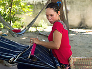 A Hindu Cham woman weaves cotton and silk fabric on a back-strap loom outside her home in My Nghiep village, Ninh Thuan province, Central Vietnam.  The resulting fabric is used to make the traditional sarong style skirt worn by Cham women on special occasions or sold to local customers in the village. The Cham people are remnants of the Kingdom of Champa (7th to 18th centuries) and are recognised by the Vietnamese government as one of Vietnam's 54 ethnic groups.