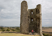 A cyclist visits the remains of Hadleigh Castle on 10th September 2019, in Hadleigh, Essex, England. Hadleigh Castle is a ruined fortification in the English county of Essex, overlooking the Thames Estuary from south of the town of Hadleigh. Built after 1215 during the reign of Henry III by Hubert de Burgh, the castle was surrounded by parkland and had an important economic and defensive role. The castle was significantly expanded and remodelled by Edward III, who turned it into a grander property,