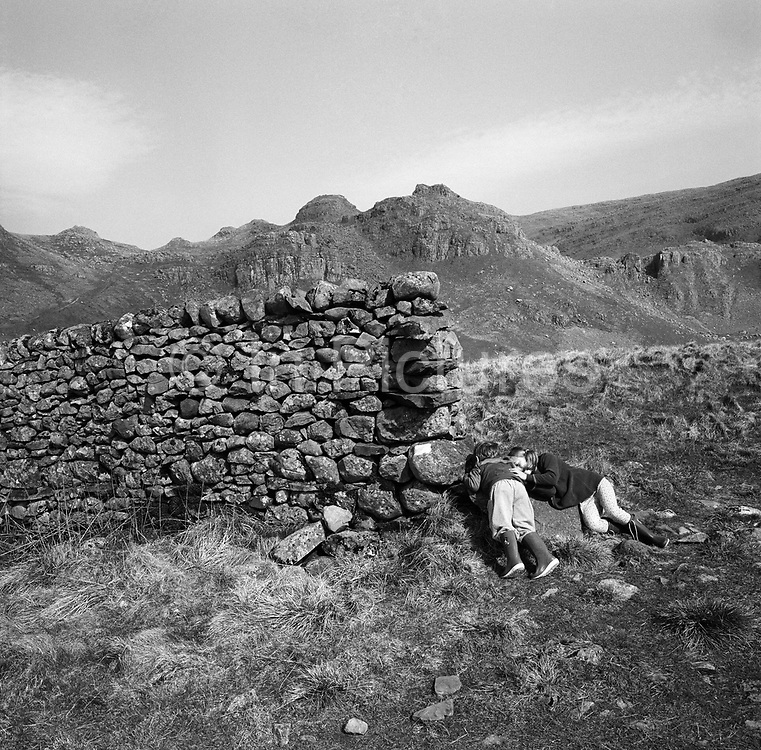 Two children lay down on the ground at the foot of a solid dry stone wall, up in the hills of the area of northern England known as the Dales, near Settle, Yorkshire. The two brother and sister have their faces against the rocks that serve as boundaries and enclosures for farmers and land owners. These walls were built by tradesmen called Wallers, a dying tradition and skill. Dry stone walls are constructed from stones without any mortar to bind them together. The wall is held up by special construction methods and by its weight. The stones must be carefully selected by shape to ensure that they have a large contact surface area with their neighbours and so do not slip. They are a legacy of the movement towards enclosure of common farming and grazing land as English society moved away from medieval feudalism. Model released.