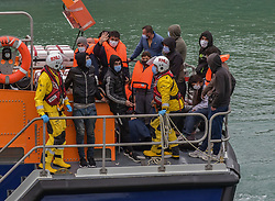 © Licensed to London News Pictures. 22/09/2021. Dover, UK.  Members of the RNLI assist migrants arriving at Dover Harbour in Kent. Migrants are continuing to attempt the crossing from France as the weather improves this week. Photo credit: Stuart Brock/LNP