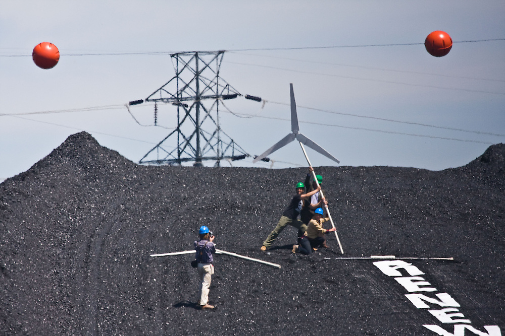 """Boulder, CO (4/27/2010) -- Four climate activists (Kate Clark, Eric Ross, Eric Bonnett and Tom Weis) climbed to the top of the large coal mound in front of the Valmont Power Plant as a rally cheered outside, deploying a banner reading """"RENEWABLES NOW"""" and erecting two mock wind turbines. The activists claimed the coal pile for about 1.5 hours before they were finally taken into custody."""