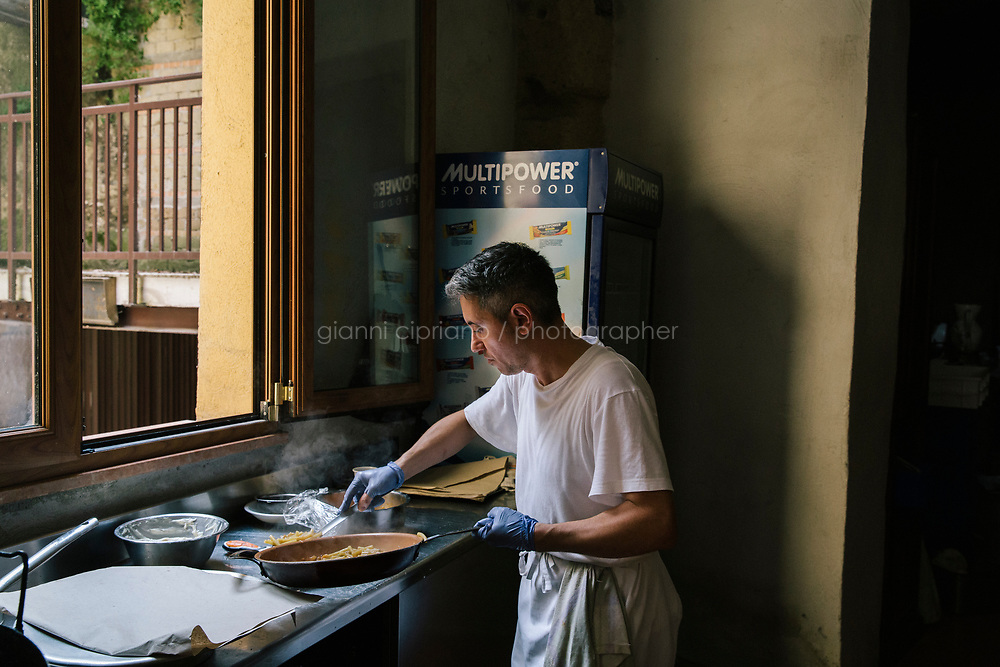 NAPLES, ITALY - 1 AUGUST 2018: Sergio, 42, cooks in the makeshift temporary kitchen of Cantina del Gallo, a family-owned restaurant in the Rione Sanità in Naples, Italy, on August 1st 2018.<br /> <br /> Cantina del Gallo, in the Rione Sanità, was established in 1898 and run by four generations of the Silvestri family. The cantina began as a store selling bulk wine and oil. It was only in the 1950s, when the legendary Aunt Cuncetta began cooking, that it became the simple and genuine tavern it is today.<br /> There are three dishes that are the restaurant's workhorses, and the ones we always seem to rotate between: the pennette alla sorrentina (a variation of the classic gnocchi alla sorrentina, seasoned with tomato, basil and stringy mozzarella), the baked cod (although the fried cod is just as mouth-watering) and the pizza cafona (peasant pizza), topped with oregano, cheese, chile and with double the tomatoes (tomato juice and chopped tomatoes).