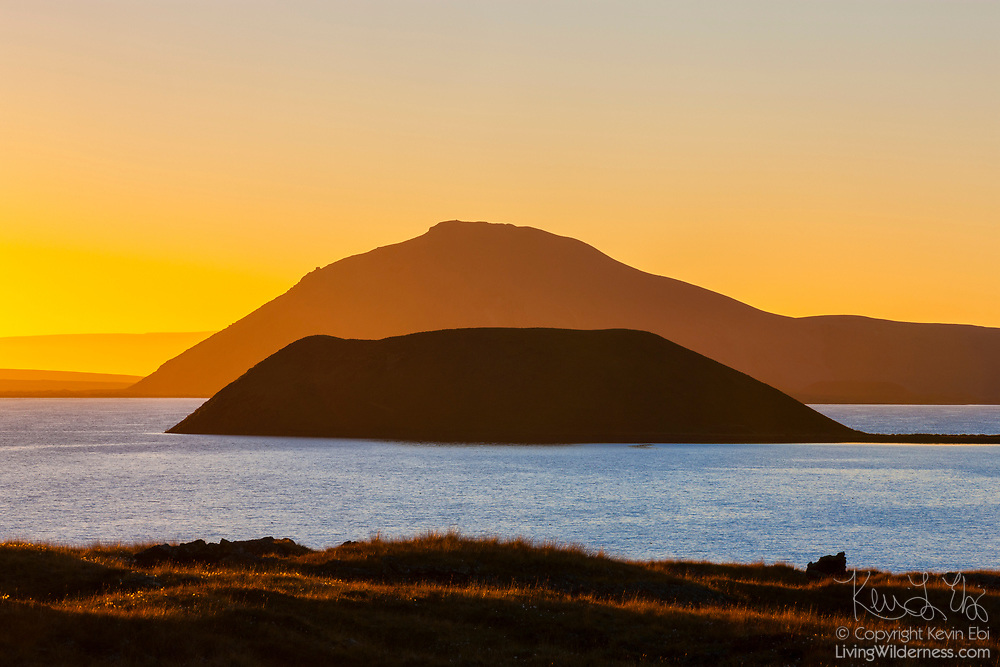 A pseudocrater is rendered in silhouette against a volanic cone at sunset in Mývatn in northern Iceland. Mývatn is a lake that was formed approximately 2,300 years ago during a volanic period. The shorter hill is a pseudocrater, also known as a rootless vent. While it resembles a volcanic cinder cone, it formed through a different process. As basaltic lava flowed over soggy lake sediments, it flash heated the moisture into vapor, causing it to blast through the lava. Mývatn means lake with midge flies; the lake is infested with them during the summer months.