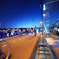 Nederland, Amsterdam , 24 oktober 2013.<br /> Verlichte en onverlichte fietsers verlaten de pont in Noord.<br /> Cyclists with light and without light cycle  at night behind Central Station.