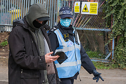 Sipson, UK. 8th March, 2021. A Metropolitan Police liaison officer uses coronavirus legislation to ask a man to vacate the area during an operation to evict residents from the remaining section of a squatted off-grid eco-community garden known as Grow Heathrow. Grow Heathrow was founded in 2010 on a previously derelict site close to Heathrow airport in protest against government plans for a third runway and has since made a significant educational and spiritual contribution to life in the Heathrow villages which are threatened by airport expansion.