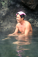 """A Japanese man relaxing at an open air hot spring called a """"rotemburo"""" in Japan.  Bathing in a natural atmosphere, among the trees and under open skies is a favorite with Japanese.  Nowadays it is almost a requirement for any hot spring resort to have outdoor baths thanks to their popularity."""