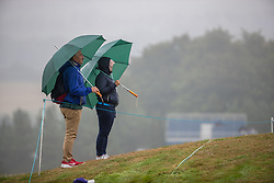Fans watch whilst taking cover from the rain at the 7th green during day eleven of the 2018 European Championships at Gleneagles PGA Centenary Course.