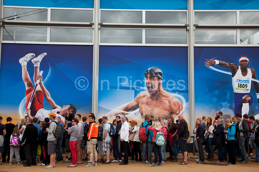 London 2012 Olympic Park in Stratford, East London. Crowds of people queue to get into the London 2012 Megastore to go shopping for related merchandise. Olympic stars Michael Phelps and Phillips Idowu adorn the building in large scale illustrations.