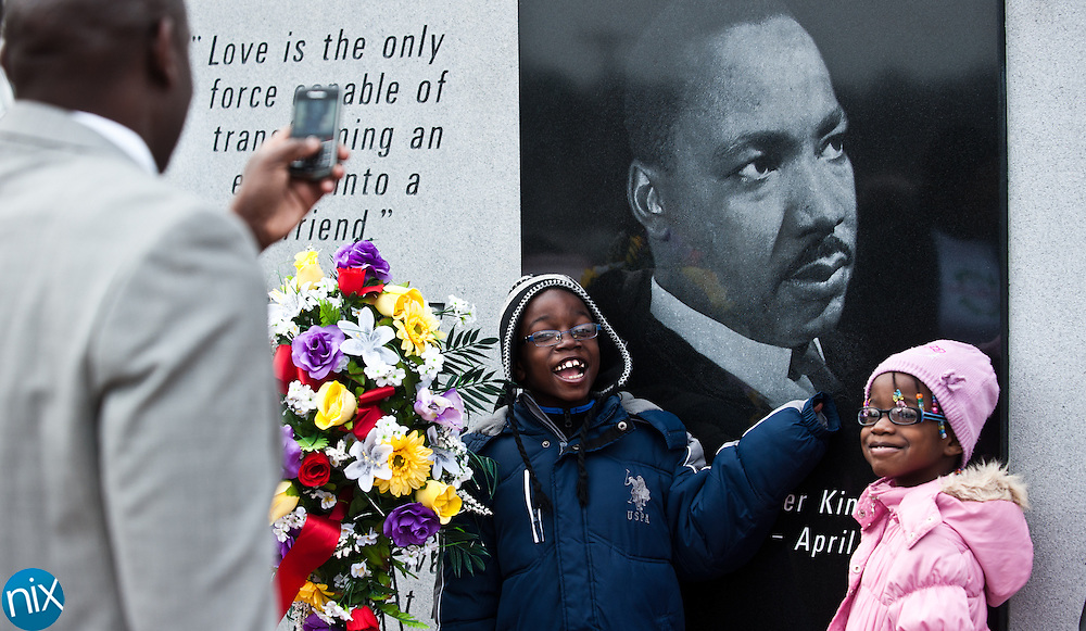 Paul Irving, a representative of Congressman Larry Kissell's office, takes a photos of his children Paul Irving Jr. and Reynn Irving during a wreath laying ceremony in honor of  Dr. Martin Luther King Jr. put on by the Logan Community Association Monday afternoon at the MLK monument in Concord. (Photo by James Nix)