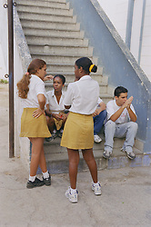 Secondary school pupils sitting on steps in playground talking,