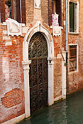 """A canal of the Venice Lagoon laps across the sill of a historic doorway shuttered with iron. Built on a sinking marsh, Venice floods often due to tides and weather. On one island, a Roman walkway is now 5 feet below sea level. Industrial pumping of groundwater (now banned) sank Venice by 10 centimeters from 1920-1970. Global warming now raises sea levels by 3.2 centimeters (1.3 inches) per decade, much faster than the marsh sediments are compacting downwards. An overwhelming consensus of world scientists agree that global warming is indeed happening and humans are contributing to it through emission of heat-trapping """"greenhouse gases,"""" primarily carbon dioxide (see www.ucsusa.org). Since the industrial revolution began, humans have increased atmospheric CO2 concentration by 35% (through burning of fossil fuels, deforesting land, and grazing livestock). The Republic of Venice wielded major sea power during the Middle Ages, Crusades, and Renaissance. Riches from Venice's silk, grain, and spice trade in the 1200s-1600s built elaborate architecture combining Gothic, Byzantine, and Arab styles. Venice and the Venetian Lagoon are honored on UNESCO's World Heritage List."""