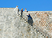 Tourists climbing steps across face of old city walls, Dubrovnik old town, Croatia