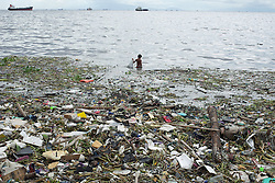 September 13, 2016 - Manila, Philippines - A Filipino boy collects garbage along the coast of Manila Bay in Navotas City, north of Manila, Philippines on Tuesday, 13 September 2016. Super typhoon Meranti is expected to hit the extreme north of the Philippines Tuesday night, and is seen to strike Taiwan on Wednesday with strong winds and flash floods. (Credit Image: © Richard James Mendoza/NurPhoto via ZUMA Press / RealTime Images)