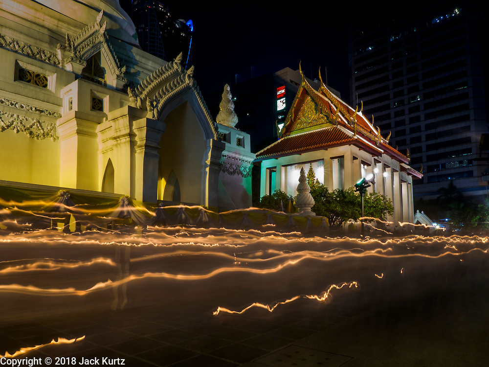 """01 MARCH 2018 - BANGKOK, THAILAND:    A time exposure of people walking in a candlelight procession around Wat Pathum Wanaram in central Bangkok. Many people go to temples to perform merit-making activities on Makha Bucha Day, which marks four important events in Buddhism: 1,250 disciples came to see the Buddha without being summoned, all of them were Arhantas, or Enlightened Ones, and all were ordained by the Buddha himself. The Buddha gave those Arhantas the principles of Buddhism. In Thailand, this teaching has been dubbed the """"Heart of Buddhism.""""    PHOTO BY JACK KURTZ"""