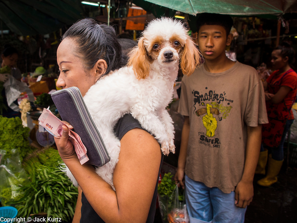 """05 APRIL 2014 - BANGKOK, THAILAND:   A woman and her dog in Khlong Toey Market in Bangkok. Khlong Toey (also called Khlong Toei) Market is one of the largest """"wet markets"""" in Thailand. The market is located in the midst of one of Bangkok's largest slum areas and close to the city's original deep water port. Thousands of people live in the neighboring slum area. Thousands more shop in the sprawling market for fresh fruits and vegetables as well meat, fish and poultry.     PHOTO BY JACK KURTZ"""