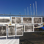 """""""Mira Mexico"""", newspaper exhibition installed on a fence by a boatyard by a former U.S. Navy Base in Seattle, Washington July 5, 2013.<br /> (Credit Image: © Kelly Mallahan)<br /> <br /> Curator<br /> Kelly Mallahan (USA)<br /> <br /> Using photographs taken by Louie Palu relating to the Mexican drug war, this project challenges the reader to take apart this newspaper to see the full photographs and view the content. The goal is to force the reader to dismantle the vehicle used to deliver news and facts and thereby empower the reader to begin to think more critically. There are 16 photos in total, eight that do not relate to violence and eight that focus on violence or the drug business.. Each photograph is printed on a single sheet of newsprint, so if you take the newspaper apart each sheet of paper will have only one photograph on each side. Only eight pictures can be viewed at one time No photo can be entirely seen unless the reader opens and takes the newspaper apart. <br /> <br /> Once the newspaper comes apart it can be put back together in any order the reader wishes. The page spreads can also be hung as an exhibition. With violent images on one side and non-violent images on the other, the reader must become editor, curator or even censor, choosing how many violent photos are seen vs. how many non-violent photographs are seen. This forces the reader to face up to the fact that all delivery of news involves choices, of what to show and tell and what not to show and tell. It also forces the reader to face up to the system of institutions that serves as the gatekeepers in journalism and the visual arts. The questions are obvious. Is the editor censoring? Is the edit a true depiction of the news and the issue? Are violent images being used effectively to tell a story, or to sensationalize the story? The actual newspaper as an object forces the reader to engage in a a multidimensional exercise in journalism, art, and the politics of representation and message man"""