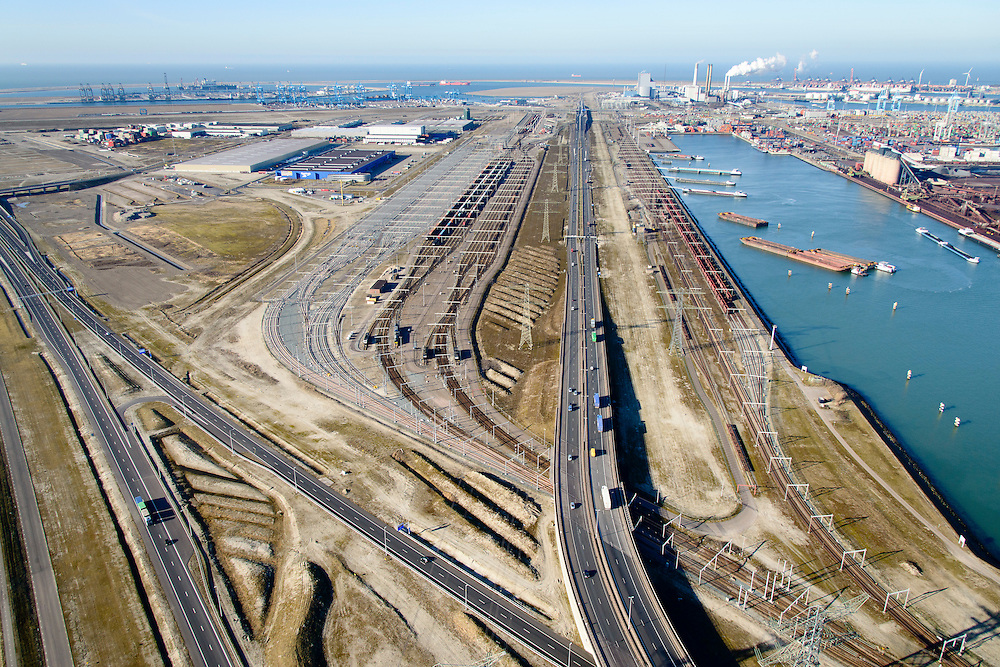 Nederland, Zuid-Holland, Rotterdam, 18-02-2015; Euopaweg buigt af naar de Maasvlakte en Tweede Maasvlakte (MV2).   Emplacement Maasvlakte, Distripark en water van de Hartelhaven. Infrabundel van autosnelweg N15, spoorweg (Betuweroute) en hoogspanningsleidingen. <br /> New and man-made land in the North sea designated for the Port of Rotterdam. Infrastructure bundle: motorway, railway (Betuweroute) and power lines.<br /> luchtfoto (toeslag op standard tarieven);<br /> aerial photo (additional fee required);<br /> copyright foto/photo Siebe Swart
