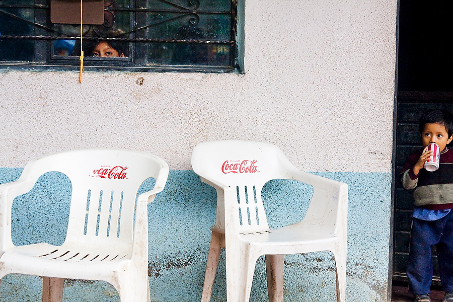 A young boy standing in a doorway drinks from a can of soda by two Coca-Cola chairs during the patron saint festival at San Pedro Chenalho, a Tzotzil Mayan village outside San Cristobal de las Casas, Chiapas, Mexico on June 27, 2008. A second child peers out from behind the window above.
