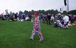 © Licensed to London News Pictures.22/08/15<br /> Castle Howard, North Yorkshire, UK. <br /> <br /> A man wearing a Union Flag suit walks amongst the crowds as hundreds of people attend the 25th anniversary of the Castle Howard Proms event near York. The theme of the event this year is a commemoration of the 75th anniversary of the Battle of Britain and the 70th anniversary of VE day and brings an evening of classic musical favourites celebrating Britishness to the lawns of Castle Howard.<br /> <br /> Photo credit : Ian Forsyth/LNP