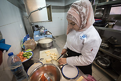 25 February 2020, Jerusalem: 21-year-old student Duha Ewiwe from 'Anata cuts cheese, as she participates in catering class at the vocational training centre in Beit Hanina. The Lutheran World Federation's vocational training centre in Beit Hanina offers vocational training for Palestinian youth across a range of different professions, providing them with the tools needed to improve their chances of finding work.