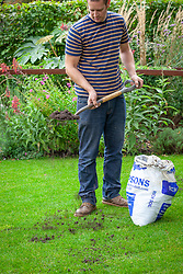 Top dressing a lawn with soil