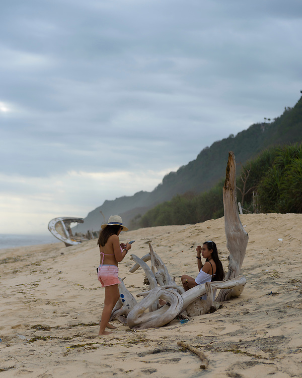Bali, Indonesia - September 12, 2017: Two young Indonesian woman who live and work on Bali visit beautiful Nunggalan Beach, home to a graffiti-covered shipwreck.