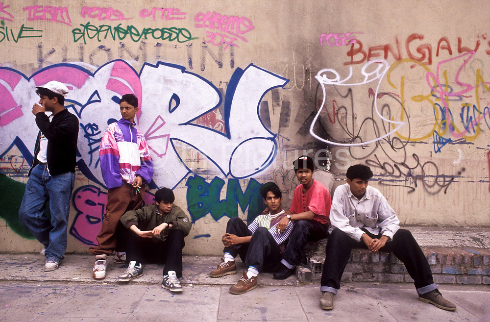 Bengali youth hang around the streets of Whitechapel with graffitti covered walls, London, UK