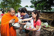 16 SEPTEMBER 2014 - SANGKHLA BURI, KANCHANABURI, THAILAND:  People present food and other offerings to Mon Buddhists monks on their morning alms rounds in the Mon community in Sangkhla Buri. The Mon were some of the first people to settle in Southeast Asia, and were responsible for the spread of Theravada Buddhism in Thailand and  Indochina. The Mon homeland is in southwestern Thailand and southeastern Myanmar (Burma). The Mon in Thailand traditionally allied themselves with the Thais during the frequent wars between Burmese and Siamese Empires in the 16th - 19th centuries and the Mon in Thailand have been assimilated into Thai culture. The Mon in Myanmar were persecuted by the Burmese government and many fled to Thailand. Sangkhla Buri is the center of Burmese Mon culture in Thailand because thousands of Mon came to this part of Thailand during the persecution.   PHOTO BY JACK KURTZ