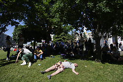 May 26, 2018 - Kiev, Ukraine - Soccer fans lay on the grass as waiting for the kick-off at the Maidan Square, near the fan zone, in doiwntown Kyiv, Ukraine,  prior to the UEFA Champions League Final between Real Madrid and Liverpool at NSC Olimpiyskiy Stadium on May 26, 2018 in Kiev, Ukraine. (Credit Image: © Maxym Marusenko/NurPhoto via ZUMA Press)